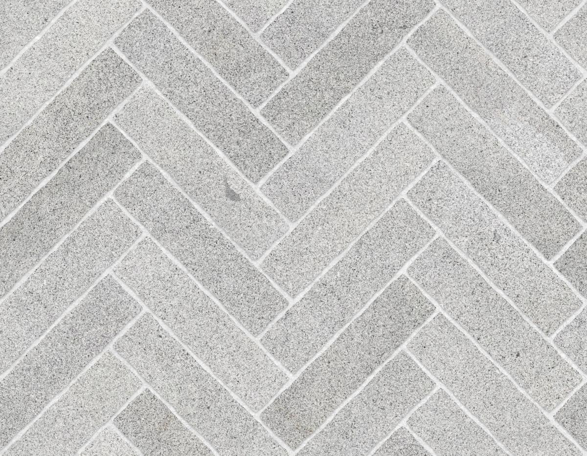 A seamless stone texture with granite blocks arranged in a herringbone pattern